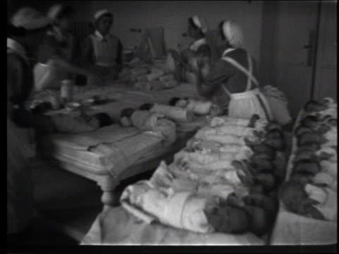 Nurses hold newborns including triplets in a crowded nursery