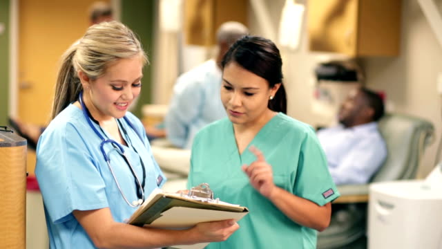 Nurses in busy hospital discussing patient chart