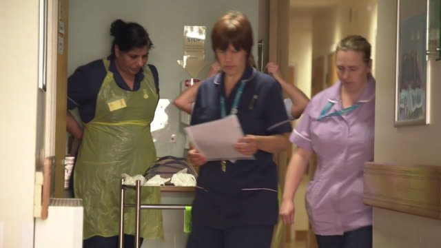 nurses inside teeside hospice putting on ppe protective equipment to treat patients during coronavirus crisis - getting dressed stock videos & royalty-free footage