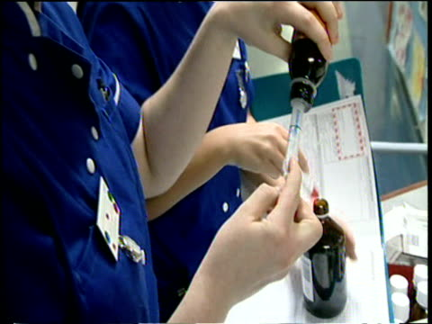 nurses on ward filling syringes with medicine and nurses doctors and medical receptionists working at nursing station chelsea and westminster hospital london - nhs stock-videos und b-roll-filmmaterial