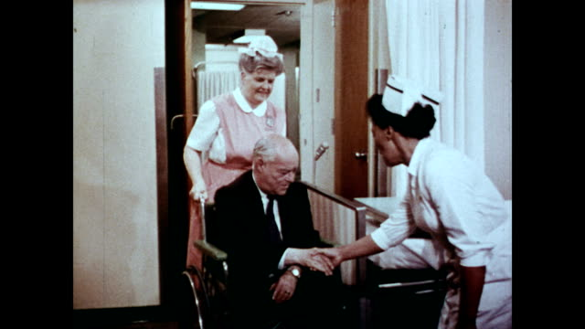 / nurses operating hospital printer and checking insurance details / senior man being wheeled into his hospital room by nurse / narrator discusses...