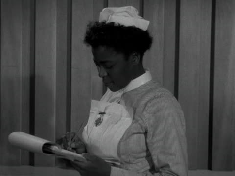 nurses reads notes on a clipboard and smiles to the camera. 1958. - nurse stock videos & royalty-free footage