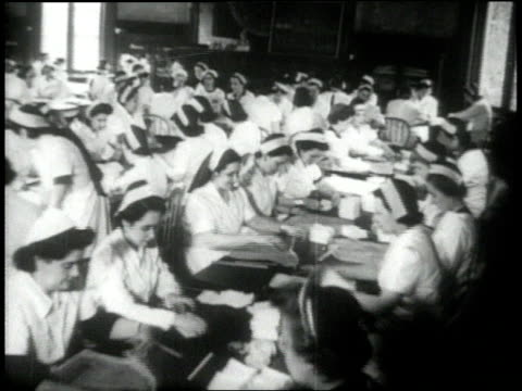 vídeos de stock e filmes b-roll de nurses sitting at tables folding bandages / nurses folding bandages / usa - transição de vídeo