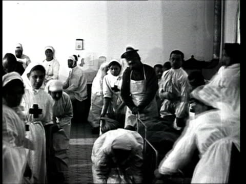 1915 montage b/w nurses taking care of wounded soldiers in war hospital during world war i/ russia - prima guerra mondiale video stock e b–roll