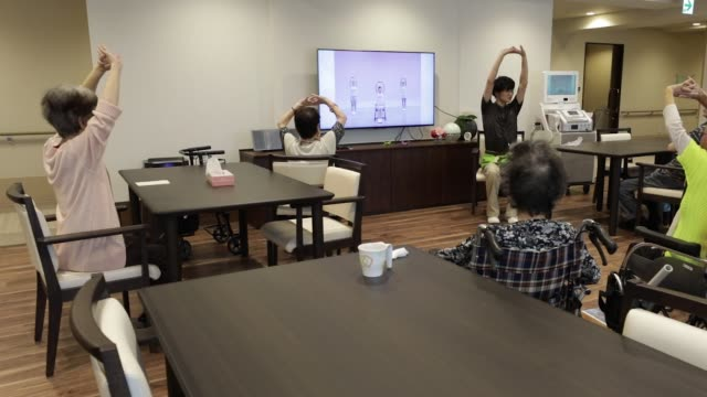 nursing care worker, right, guides residents during an stretching session at the as partners co. asheim nerima garden nursing home in tokyo, japan,... - 介護点の映像素材/bロール