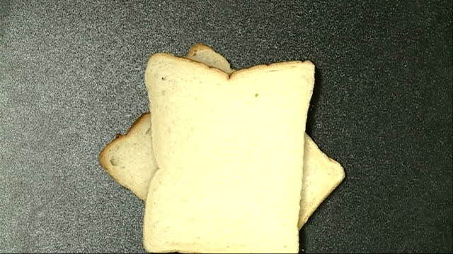 sliced white bread; england: int close shots of slices of white bread as piled up on table - slice stock videos & royalty-free footage
