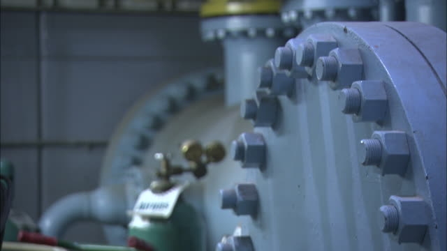 nuts and bolts secure valves in an equipment room. - bolt stock videos & royalty-free footage