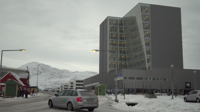 Nuuk Centre shopping centre and housing block with Greenland and Denmark flags outside