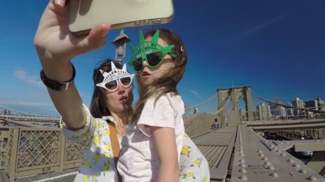 stockvideo's en b-roll-footage met nyc-reizigers. gelukkig toeristische nemen selfie in new york city. - modeweek