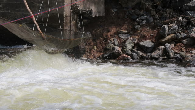 nylon mesh tie fish trap over the flowing water. - netting stock videos and b-roll footage
