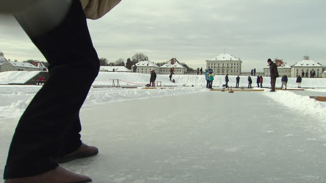 Nymphenburg, curling stick slips over ice, legs of a man, people in background