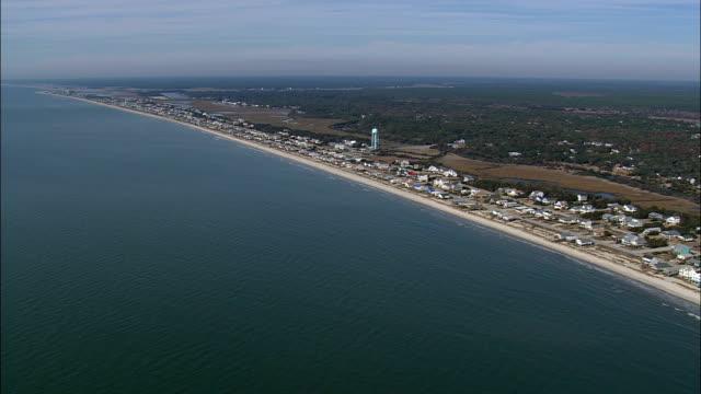 oak island and beach side homes  - aerial view - north carolina,  brunswick county,  united states - north carolina beach stock videos & royalty-free footage