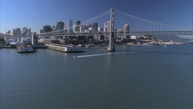 LOW AERIAL Oakland Bay Bridge and skyscrapers of San Francisco / California, USA