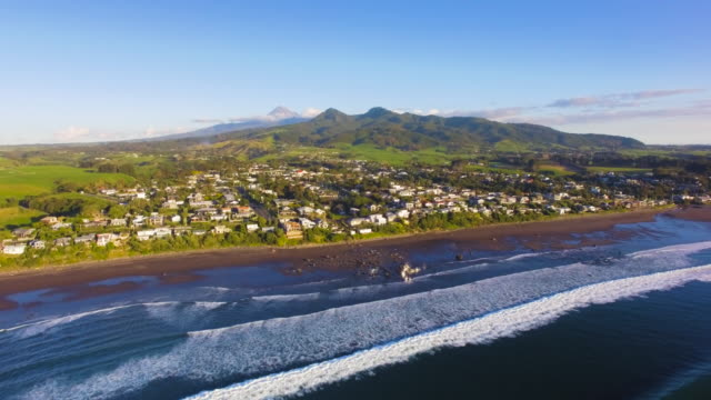 oakura town aerial view from oakura beach and mt taranaki in background. - north island new zealand stock videos & royalty-free footage
