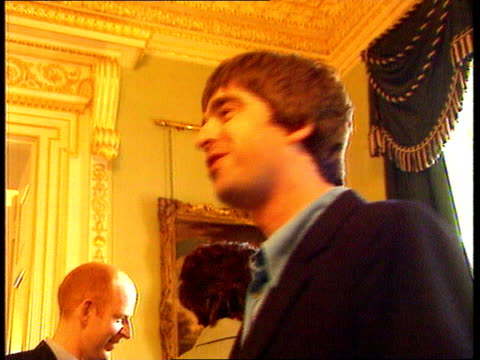 oasis asian tour; a)c4n lib england: london: downing st: no.10: seq noel gallagher chatting at no.10 party - オアシス点の映像素材/bロール