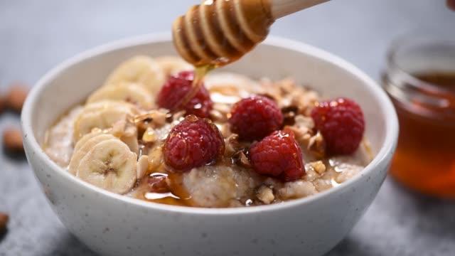 oatmeal porridge with honey, berries - oatmeal stock videos & royalty-free footage