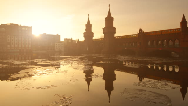 Oberbaumbrücke Berlin Winterscape with Reflection Ice and Sunset on the Spree River and Train Speed