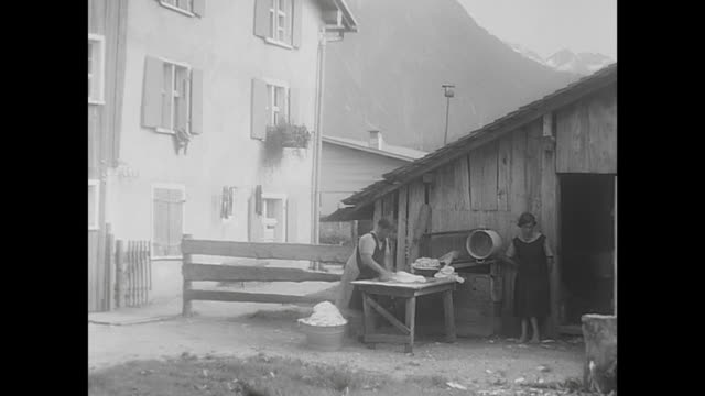 oberstdorf 1933 typical city in the alps little boy jumps happy dressed with leather trousers and a hat 2 woman washing the laundry in front of a... - alpi video stock e b–roll
