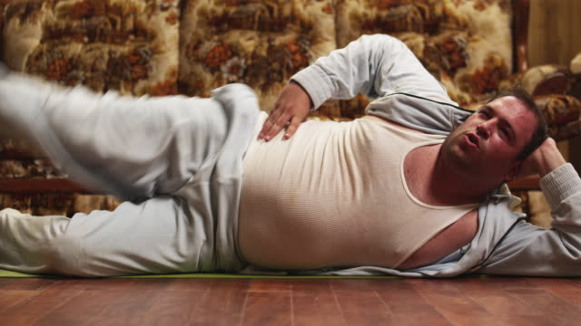 MS Obese man exercising in living room floor / Orem, Utah, USA