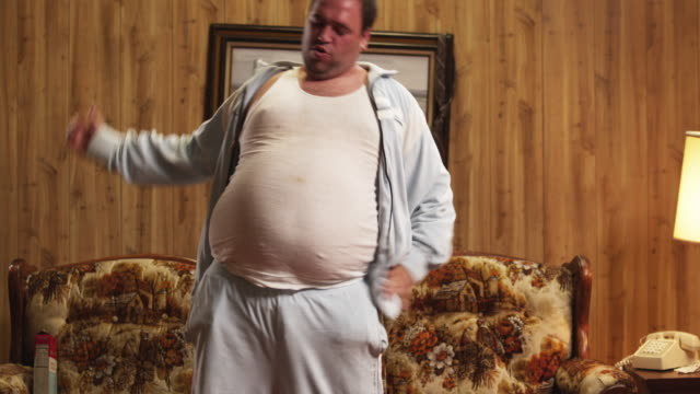 MS TU Obese man stretching and exercising in living room / Orem, Utah, USA