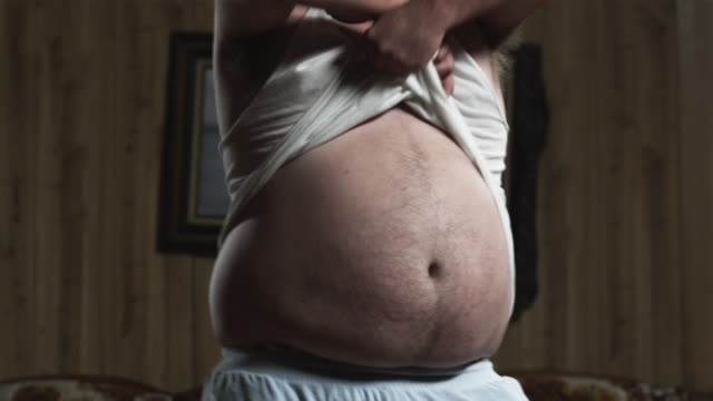 MSTU SLO MO Obese man undressing while dancing in living room / Orem, Utah, USA