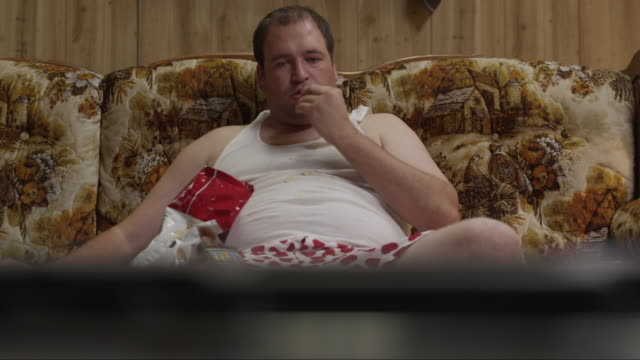 MS TU Obese man wearing underwear eating potato chips, watching TV on sofa / Orem, Utah, USA