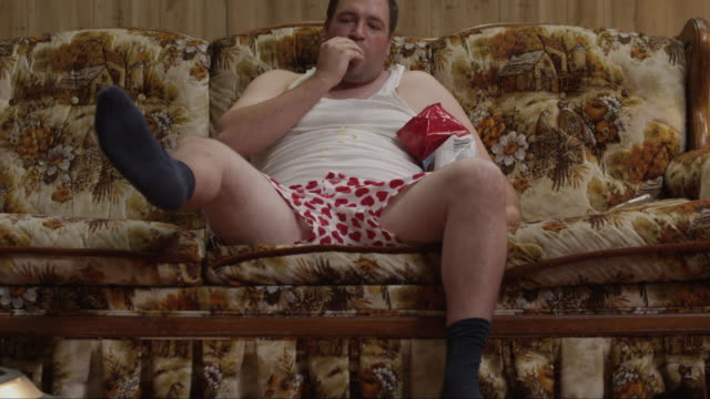 MS TU Obese man wearing underwear sitting on sofa while another man vacuuming floor / Orem, Utah, USA