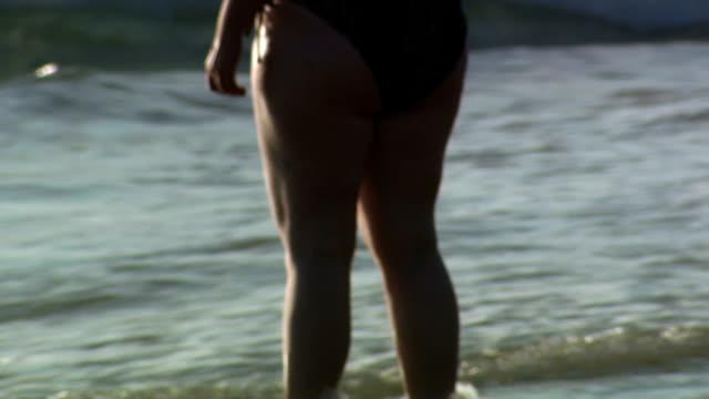 obese woman standing in water in bikini - dicke frauen am strand stock-videos und b-roll-filmmaterial