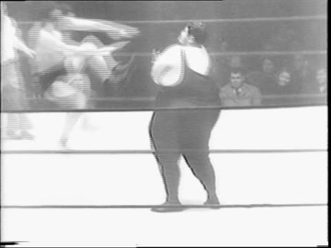 Obese wrestler Martin 'The Blimp' Levy makes face at camera / Levy doing stretches / man measuring Levy's waist / Levy enters ring wrestles Pierre...