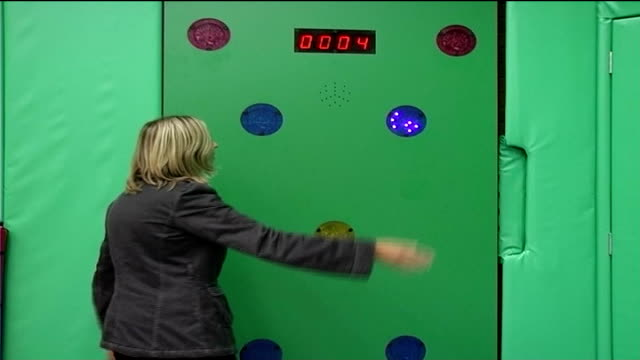london's first child-only gym opens; reporter to camera at sports training wall testing hand-eye co-ordination - co ordination stock videos & royalty-free footage