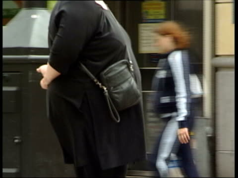 doctors propose fat tax news fat woman along street pan cms fat woman along towards - overweight doctor stock videos & royalty-free footage