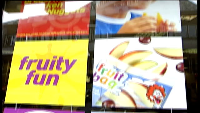 Hospital allows McDonalds to hand out free burgers ITN Children seen eating in McDonalds restaurant thru window PULL OUT CMS Posters in window...