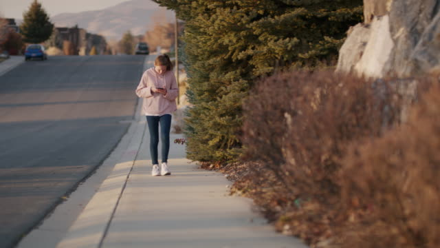oblivious girl walking on neighborhood sidewalk texting on cell phone / cedar hills, utah, united states - oblivious stock videos & royalty-free footage