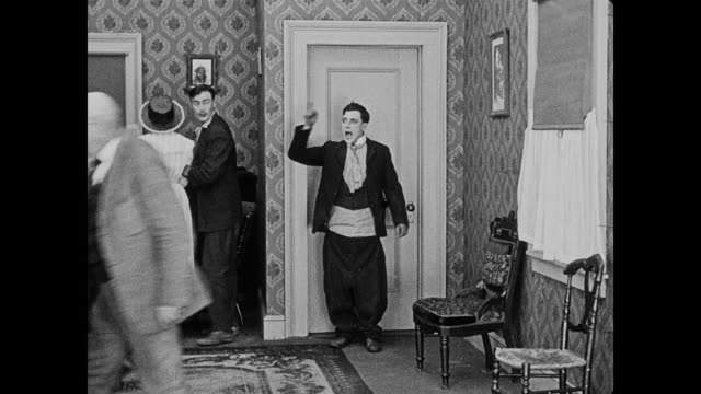 1920 oblivious, man (buster keaton) gives speech to shocked and crowded room at his wedding as his over-sized pants begin to fall down - rede stock-videos und b-roll-filmmaterial