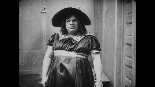 1917 oblivious man (fatty arbuckle) in drag scares men showering in bathhouse until he is removed by angry lifeguard - fatty arbuckle stock videos and b-roll footage