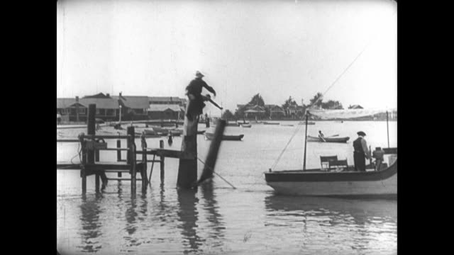 1921 oblivious man (buster keaton) launches boat from pier, taking pier and fisherman along for the ride - oblivious stock videos & royalty-free footage