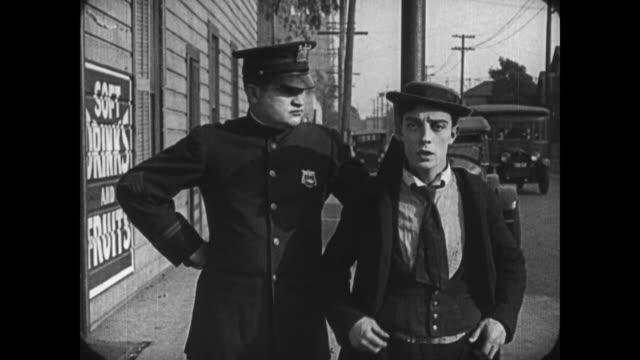 1921 oblivious man (buster keaton) puts jacket on around lamppost fearing police intervention - 1921年点の映像素材/bロール