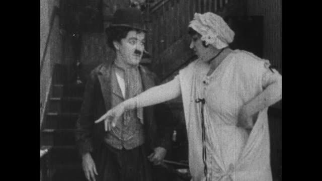 vídeos de stock, filmes e b-roll de 1915 oblivious pointing woman continually knocks charlie chaplin's hat off his head - charlie chaplin