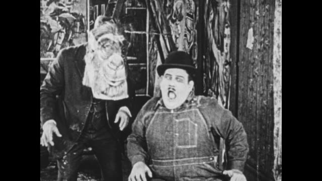 1925 oblivious wallpaper assistant pastes monkey poster to man's face, who then awakens and frightens the manager (oliver hardy) with his appearance - sticky stock videos & royalty-free footage