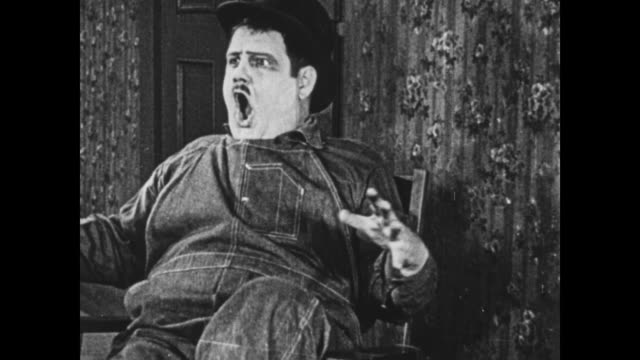 1925 oblivious wallpaper helper pulls full size ladder from bag, hitting surprised onlooker as his boss (oliver hardy) reacts - careless stock videos & royalty-free footage