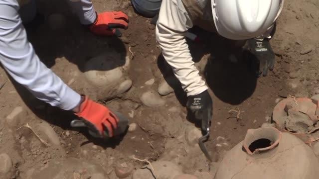 obreros que excavaban una calle de lima para instalar una tuberia de gas descubrieron un cementerio de 1800 anos de antiguedad informaron arqueologas... - arqueologia stock videos & royalty-free footage