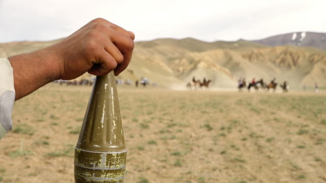 observer watches group of men play horse mounted game resting his hand on the top of a rocket warhead. - rocket launcher stock videos & royalty-free footage