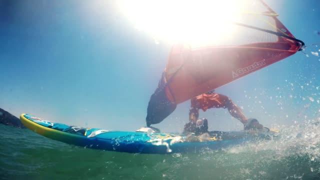 pov ein windsurfer reiten bei sonnenschein zu beobachten - windsurfen stock-videos und b-roll-filmmaterial