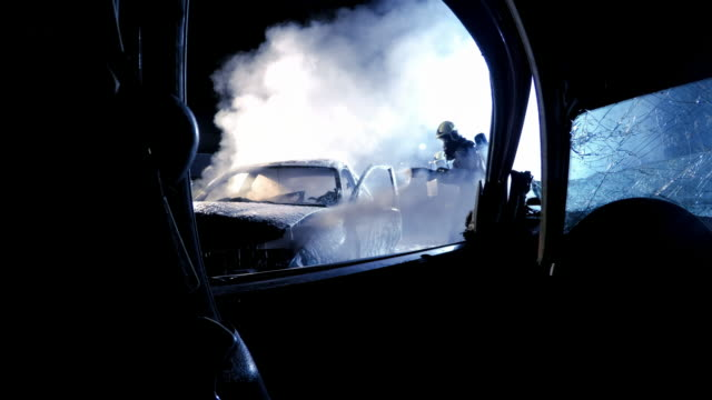 POV Observing the firefighter splashing foam onto a car that caught fire in a car crash at night