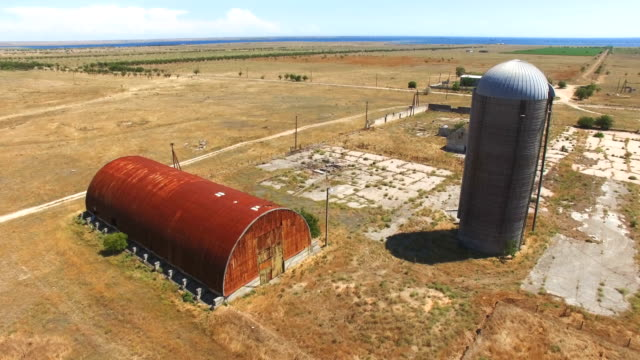 aerial: obsolete grain storage bin and grain elevator - elevator point of view stock videos and b-roll footage