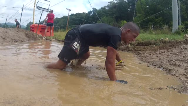 obstacle race spartan entrants pushed to limits in mud puddle to barbed wire - salmini stock videos & royalty-free footage