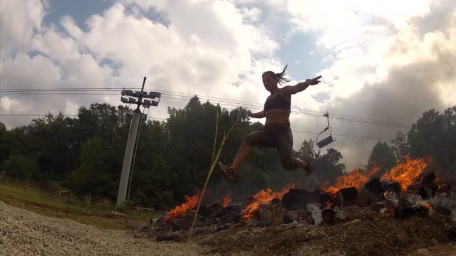 obstacle race spartan entrants pushed to limits jump over fire pit - salmini stock videos and b-roll footage