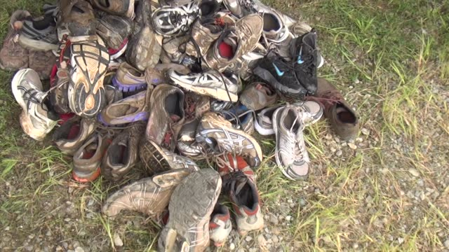 obstacle race spartan entrants pushed to limits shoes in pile donated after race - salmini stock videos and b-roll footage