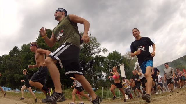 obstacle race spartan entrants pushed to limits start from low angle - salmini stock videos and b-roll footage