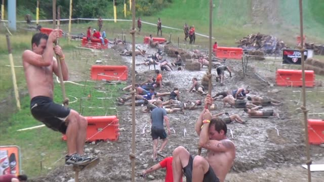 obstacle race spartan entrants pushed to limits under barbed wire zoom to rope climb - salmini stock videos and b-roll footage